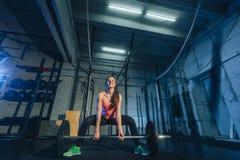 举在健身房的肌肉年轻健身妇女重量crossfit 健身妇女deadlift杠铃 Crossfit妇女 库存照片