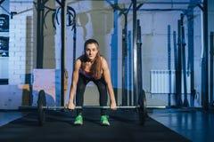 举在健身房的肌肉年轻健身妇女重量crossfit 健身妇女deadlift杠铃 Crossfit妇女 免版税库存照片