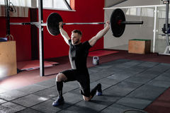举在健身房的适合的年轻运动员杠铃 免版税库存图片