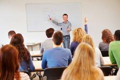 举手的学员在学校 库存照片