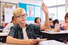 戴举在小学类的眼镜的男孩手 免版税库存图片