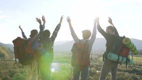 举在山上面的小组年轻活跃成功的人民手 有胳膊的徒步旅行者被举在山顶部 远足者 股票视频