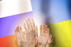 举在旗子俄罗斯和乌克兰背景的人们手 冲突概念 库存图片