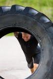 举在街道上的运动员大拖拉机轮胎 库存图片