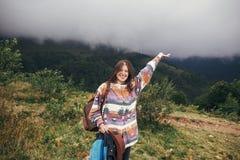 举在迷雾山脉的愉快的旅客行家女孩手 Su 免版税图库摄影