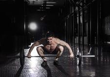 举在crossfit健身房的肌肉人杠铃 免版税库存照片