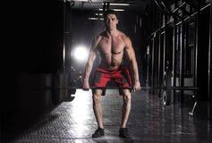举在crossfit健身房的肌肉人杠铃 库存照片