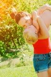 举她的儿子的年轻深色的母亲在获得的公园乐趣享受母性 库存图片