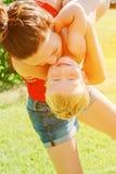 举她的儿子的年轻深色的母亲在获得的公园乐趣享受母性 免版税库存照片