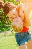 举她的儿子的年轻深色的母亲在获得的公园乐趣享受母性 免版税库存图片