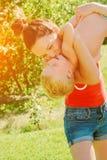 举她的儿子的年轻深色的母亲在获得的公园乐趣享受母性 库存照片