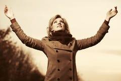 举她的在天空的愉快的年轻时尚妇女手 库存照片