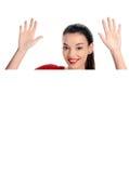 举她的手的一名美丽的愉快的妇女的画象。在一张白色空白的海报后。 库存照片