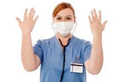 举她的胳膊的女性外科医生 免版税图库摄影
