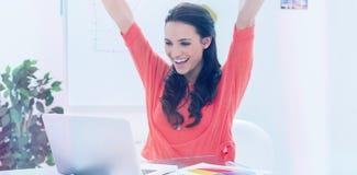 举她的胳膊的激动的妇女,当研究她的膝上型计算机时 库存图片
