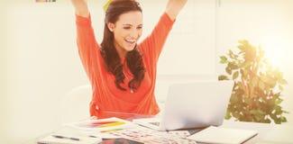 举她的胳膊的激动的妇女,当研究她的膝上型计算机时 库存照片