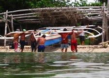 举小船的人靠码头 免版税库存图片