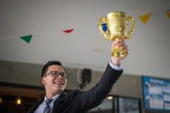 举手和拿着一个金黄战利品杯子的亚洲商人对快乐和庆祝他的成功在事业和使命 库存图片