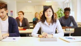 举手的亚裔学生在教室 免版税库存照片