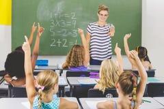 举手的学校孩子在教室 库存图片