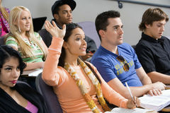 举手的学生在类演讲期间 免版税库存照片