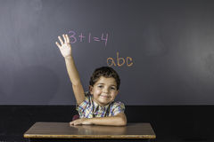 举手的孩子在教室。 免版税库存照片