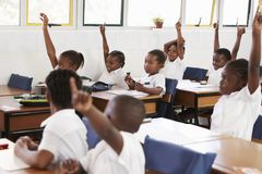举手的孩子在教训期间在一所小学 库存照片