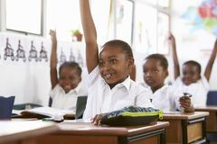 举手的孩子在教训期间在一所小学 免版税图库摄影