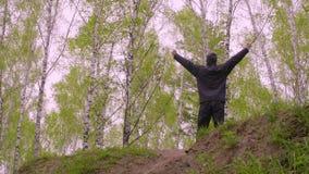 举手的快乐的人站起来在桦树背景的高地 股票录像