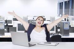 举手的快乐的妇女在办公室 免版税库存照片