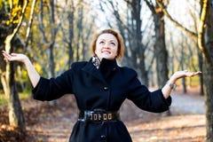 举手的愉快的少妇在秋天公园 免版税库存照片