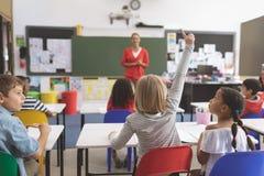 举手的白种人女小学生,当他的同学在看她时的她旁边 免版税库存照片