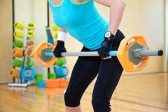 举的概念-行使与在健身房的杠铃的妇女 免版税库存图片