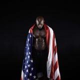 举着一面美国国旗的男性运动员 图库摄影