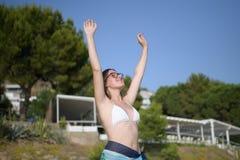举胳膊的愉快的年轻女人佩带的比基尼泳装的侧视图画象 免版税图库摄影