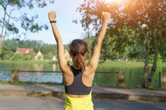 举胳膊的愉快的成功的女运动员对在金黄后面照明设备日落夏天的天空 有胳膊的健身运动员 库存照片