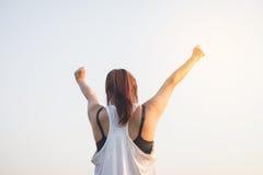 举胳膊的愉快的成功的女运动员对在金黄后面照明设备日落夏天的天空 免版税库存图片
