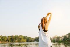 举胳膊的愉快的成功的女运动员对在金黄后面照明设备日落夏天的天空 库存图片
