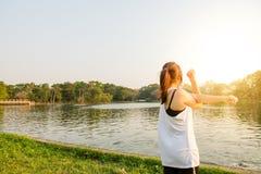 举胳膊的愉快的成功的女运动员对在金黄后面照明设备日落夏天的天空 库存照片
