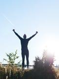 举胳膊的成功的人在十字跟踪赛跑以后 免版税库存照片