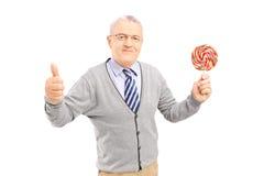 举行一个五颜六色的棒棒糖和给的微笑的绅士拇指u 免版税库存图片