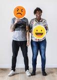 举行一个传神意思号面孔表情的人种间夫妇皱眉并且微笑关系问题概念 免版税图库摄影