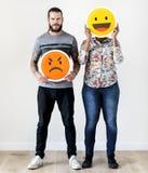 举行一个传神意思号面孔表情的人种间夫妇皱眉并且微笑关系问题概念 免版税库存图片