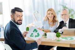 举行一个回收的标志的愉快的人,当坐与他的同事时 免版税图库摄影