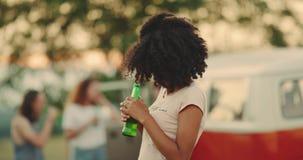 举行一个瓶啤酒微笑的愉快看的野餐的非洲少妇对照相机 股票视频