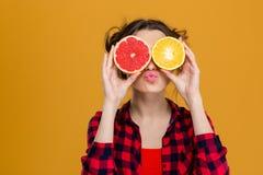 举行一半柑橘水果的滑稽的嬉戏的妇女反对眼睛 免版税库存照片