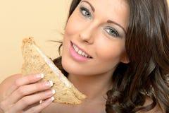 举行一半的健康妇女在黑面包的一个大虾三明治 库存图片