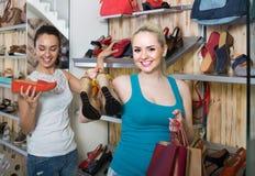 举行一双被采摘的鞋在精品店的女孩 库存图片
