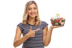 举行一小手提篮和指向的妇女 免版税库存照片
