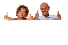 举行一张空白的招贴的年轻夫妇。赞许。 库存图片